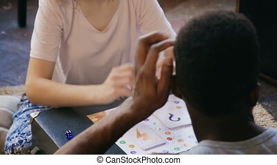 Multiracial couple playing the board game together. Man and...