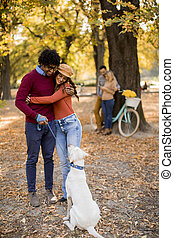 Multiracial couple walking with dog in autumn park