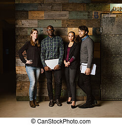 Multiracial creative team posing for camera in office