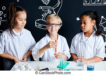 Multiracial diverse kids with test tubes studying chemistry at school laboratory