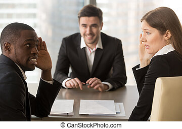Multiracial employers hiding faces, discussing job applicant...