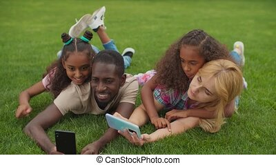 Multiracial family taking selfie lying on grass - Positive ...