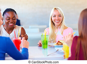 multiracial female friends enjoying meal in restaurant