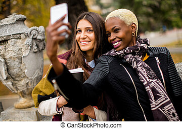 Multiracial female friends taking selfie outdoor