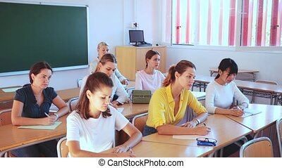 Students doing test in college, writing in notepads during lesson