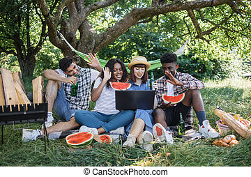Multiracial friends having video call on laptop outdoors
