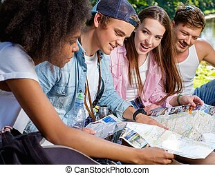 Multiracial friends tourists in a park with map