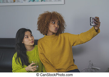 Multiracial friendship. Asian and african american black woman taking selfie using smartphone