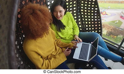 Multiracial friendship. Young african american and asian women gossiping on the swing on the terrace and browsing social media on the laptop. High quality 4k footage