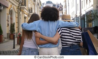 Multiracial girls embracing while shopping - Rear view of...