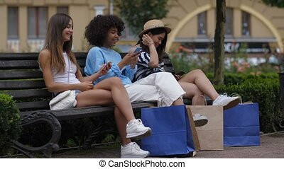 Multiracial girls with phones resting on the bench - Happy...