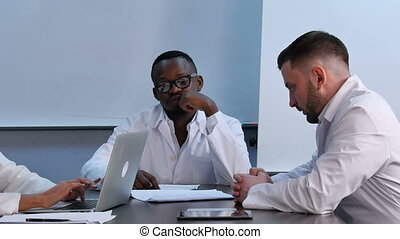 Multiracial group of doctors having discussion in office
