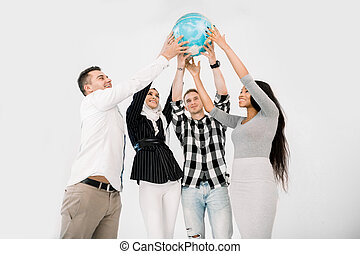Multiracial group of four young cheerful people holding up the Earth Globe. Young people holding up a globe standing on white background