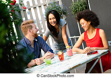 Multiracial group of friends having fun and talking in restaurant
