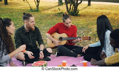 Multiracial group of friends is playing the guitar, singing...
