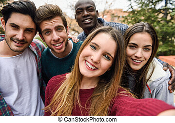 Multiracial group of friends taking selfie in a urban park ...