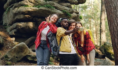 Multiracial group of friends tourists are taking selfie in...