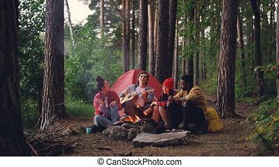 Multiracial group of friends travelers is singing songs in...