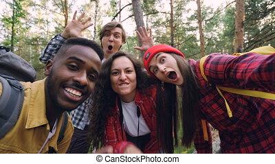 Multiracial group of friends travelers is taking selfie in...