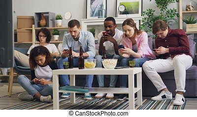 Multiracial group of friends using smartphones touching...