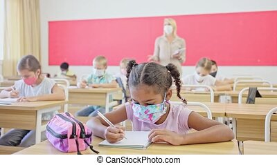 School children in protective face masks writing test, smart young people studying at primary school during pandemic