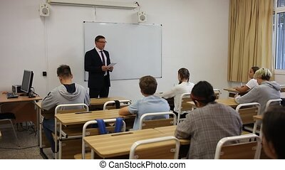 Group of focused teenage students sitting at classroom working at class with helpful teacher