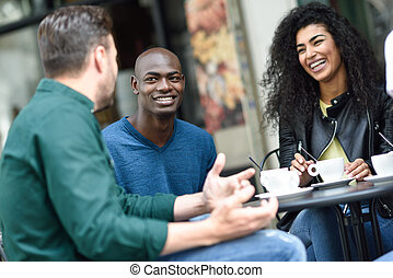 Multiracial group of three friends having a coffee together....