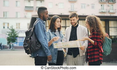 Multiracial group of tourists is looking at paper map...