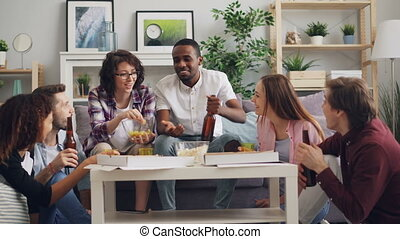 Multiracial group of young people celebrating at home with pizza and alcohol
