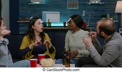Multiracial group playing Guess who game with sticky papers attaching to foreheads. Multi-ethnic friends having fun, laughing together while sitting on sofa in living room late at night