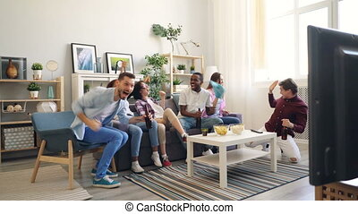 Multiracial group watching sports on TV at home cheering...