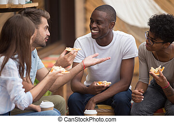 Multiracial happy friends laughing at joke eating pizza in cafe