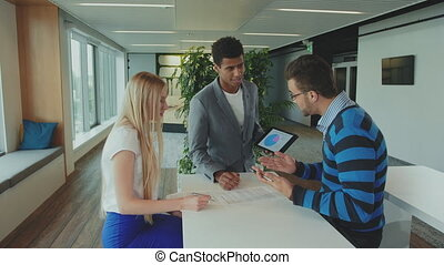 Multiracial men and woman working on report. Group of diverse woman and men with tablet in modern office hall having work with documents and statistics.