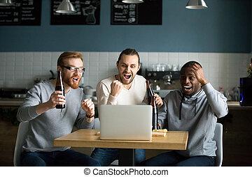 Multiracial men drinking beer celebrating victory watching game