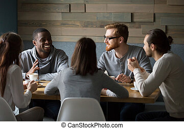 Multiracial millennial friends talking drinking coffee together