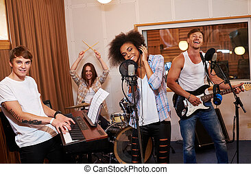 Multiracial music band performing in a recording studio.