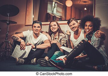 Multiracial music band performing in a recording studio -...
