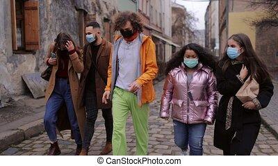 Multiracial people in masks walking on street