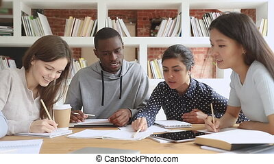 Multiracial college university students group study together prepare project make notes, happy diverse young people team write essay summary learn in teamwork do creative research homework in library