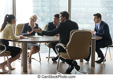 Multiracial team group disputing in office boardroom at meeting