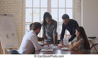 Corporate teamwork brainstorm concept, focused multiracial team talk share ideas working together on new business plan at office briefing, diverse workers group discussing paperwork at meeting table