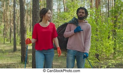 Environmentally aware multiracial volunteer couple with tools in protective gloves carrying garbage bag, walking through forest and picking up garbage. Environment protection and care for nature.