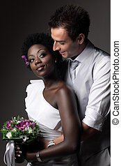 Multiracial wedding couple posing in a studio