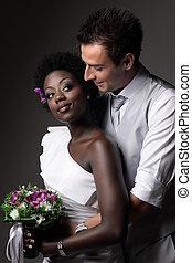 Multiracial wedding couple posing in a studio