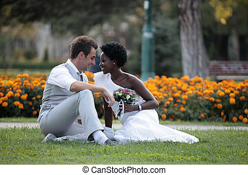 Multiracial wedding couple posing on the grass in the park