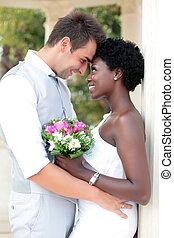 Multiracial wedding couple posing outdoors