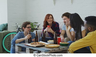 Multiracial young cheerful friends enjoying sitting together and talking each other while drinking beer and eating snacks at home