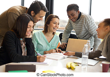 Multiracial young people enjoying group study at table....