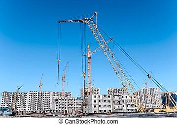 Multistorey housing under construction and construction cranes
