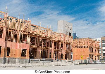 Multistory condominium building under development with elevator shaft and metal fencing near Dallas